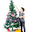 Asicute boy with gift box ,decorate Christmas tree . — Stock Photo #34458727