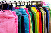 Colorful long pants jean with hangers — Stock Photo