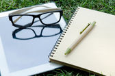 Office supplies Notebook paper tablet and glasses — Stock Photo