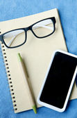 Office supplies Notebook paper smartphone and glasses — Stock Photo