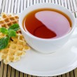 Tea with waffle and mint on Bamboo place mat — Stock Photo