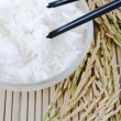 Bowl of white steamed rice with chopsticks on bamboo mat.with pa — Stock Photo