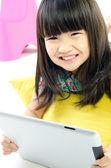 Um sorriso de menina asiática com computador tablet — Fotografia Stock