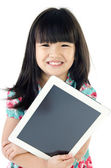 Little asian girl smiles with tablet computer — Stock Photo