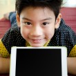 Stock Photo: Little asiboy smiles with tablet computer acting on his face