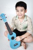 Asian child  with his ukulele — Stock Photo