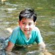 Young cute boy playing in the water in a beautiful river — Stock Photo #50071207