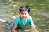 Young cute boy playing in the water in a beautiful river — Photo