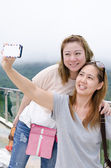 Beautiful young women using a mobile phone. Portrait of asian. — Stock Photo