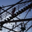 Stock Video: Families play on large gorillclimb ropes course silhouette 2