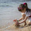 Little girl playing on the beach — Stok fotoğraf