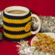 Cup in knit cover with tea and Christmas cookies — Stock Photo
