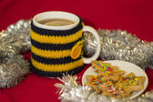 Cup in knit cover with tea and Christmas cookies — Foto de Stock