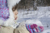 Little girl blowing on snow in hands — Stock Photo