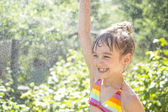Little girl in a spray of water in summer — Stock Photo