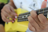 Closeup of a woman playing ukulele. — Stock Photo