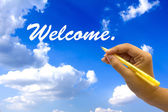 Hand writing welcome on blue sky. — Stock Photo