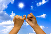 Two coupled hands on blue sky. — Stock Photo