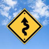 Kurven voraus warnzeichen auf schönen himmel hintergrund. — Stockfoto