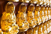 Many small Buddha statue on the wall at chinese temple, Thailand — Stock Photo