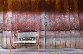 Chinese old building exterior with door and single chair in Thai — Stock Photo
