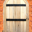 Stock Photo: Old style wooden door on brick wall