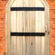 Old style wooden door on brick wall — Stock Photo