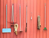 Farm tools hang on red barn wall — Stock fotografie