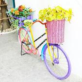 Umělé květiny a starožitné kolo pro dekorace, vintage — Stock fotografie