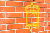 Yellow Birdcage on brick wall background. — Stock Photo