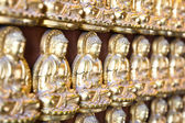 Ten Thousand Golden Buddhas lined up along The wall of Chinese T — Stock Photo