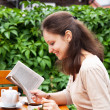 The beautiful girl in a summer cafe reading a book — Stockfoto