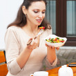 Beautiful girl eats vegetable salad — Stock Photo