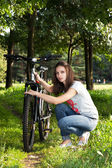 The girl repairing a bicycle wheel — Stock Photo
