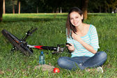 Woman relaxing in the park on the lawn — Stock Photo
