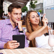 Girl with  guy in  cafe used  tablet computer — Stock Photo