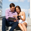 Stock Photo: Girl and boy sitting on stairs with tablet computer
