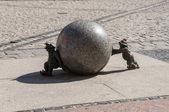 Stone dwarfs pushing the ball. — Stock Photo