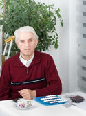 Portrait of senior man with pills — Stock Photo