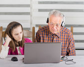Girl and old man on laptop — Stock Photo