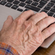 Old man using laptop — Stock Photo