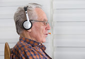 Old man with headset — Stock Photo