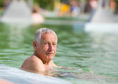 Old man in pool — Stock Photo