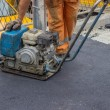 Asphalt worker with compactor plate — Stock Photo