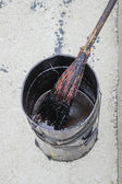 Bitumen Emulsion in metal bucket which is applied with a broom — Stock Photo