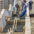 Stock Photo: Manual workers pouring concrete steps 2