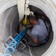 Worker inside a manhole - working in a manhole — Stock Photo #31210305