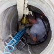 Worker inside a manhole - working in a manhole — Stock Photo