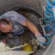 Worker inside a manhole, working in a manhole 2 — Lizenzfreies Foto