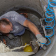 Worker inside manhole, working in manhole 2 — Stock Photo #31210315